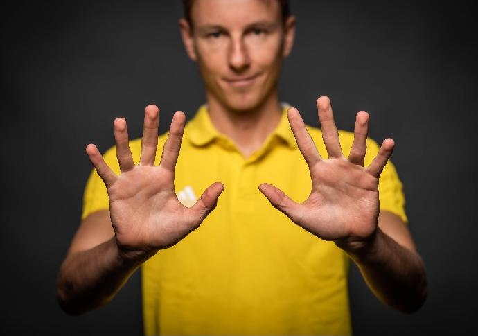Portrait von Physiotherapeut Frank Friedrichmit von sich gestreckten Händen.